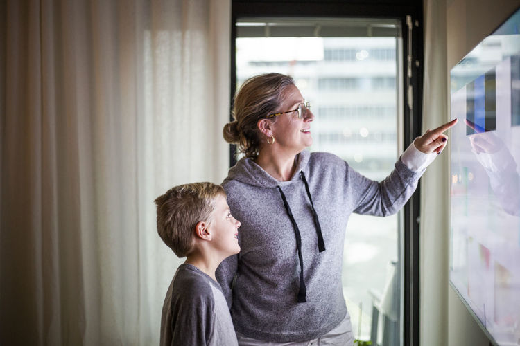 Boys looking away while standing on window