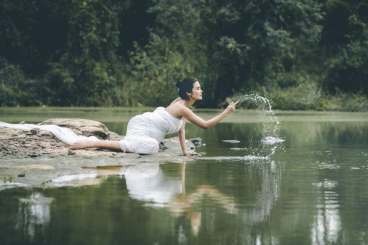Woman splashing water in lake against trees