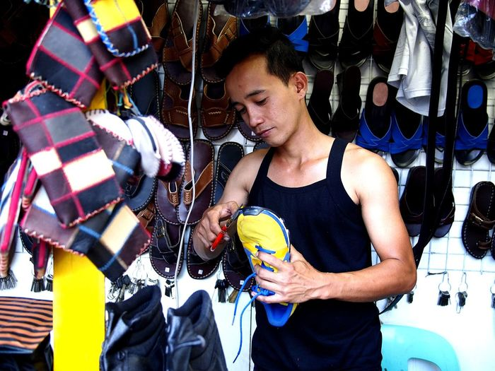 shoe repair man fixing a rubber shoe in his shop Man Males  Human person Asian  Filipino Work Worker Working Professional Professional Occupation Shoe Shoes Shoe Repair Rubber Shoes Fix  Repair Shop Repairs Footwear Occupation Portrait Shoe Store Shoelace Canvas Shoe