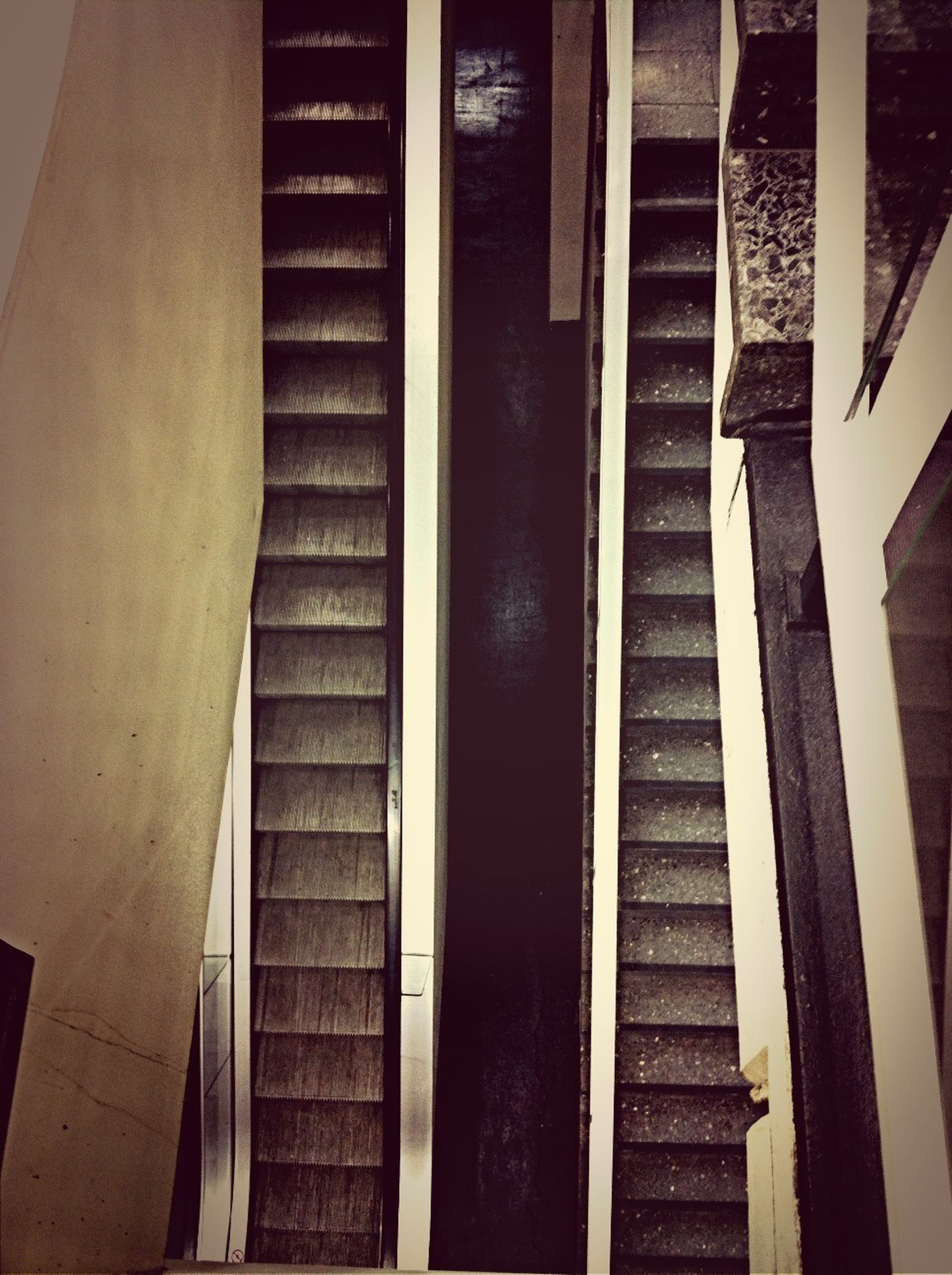 indoors, steps, high angle view, steps and staircases, staircase, railing, architecture, built structure, modern, low angle view, escalator, in a row, no people, illuminated, metal, building, diminishing perspective, reflection, repetition, empty