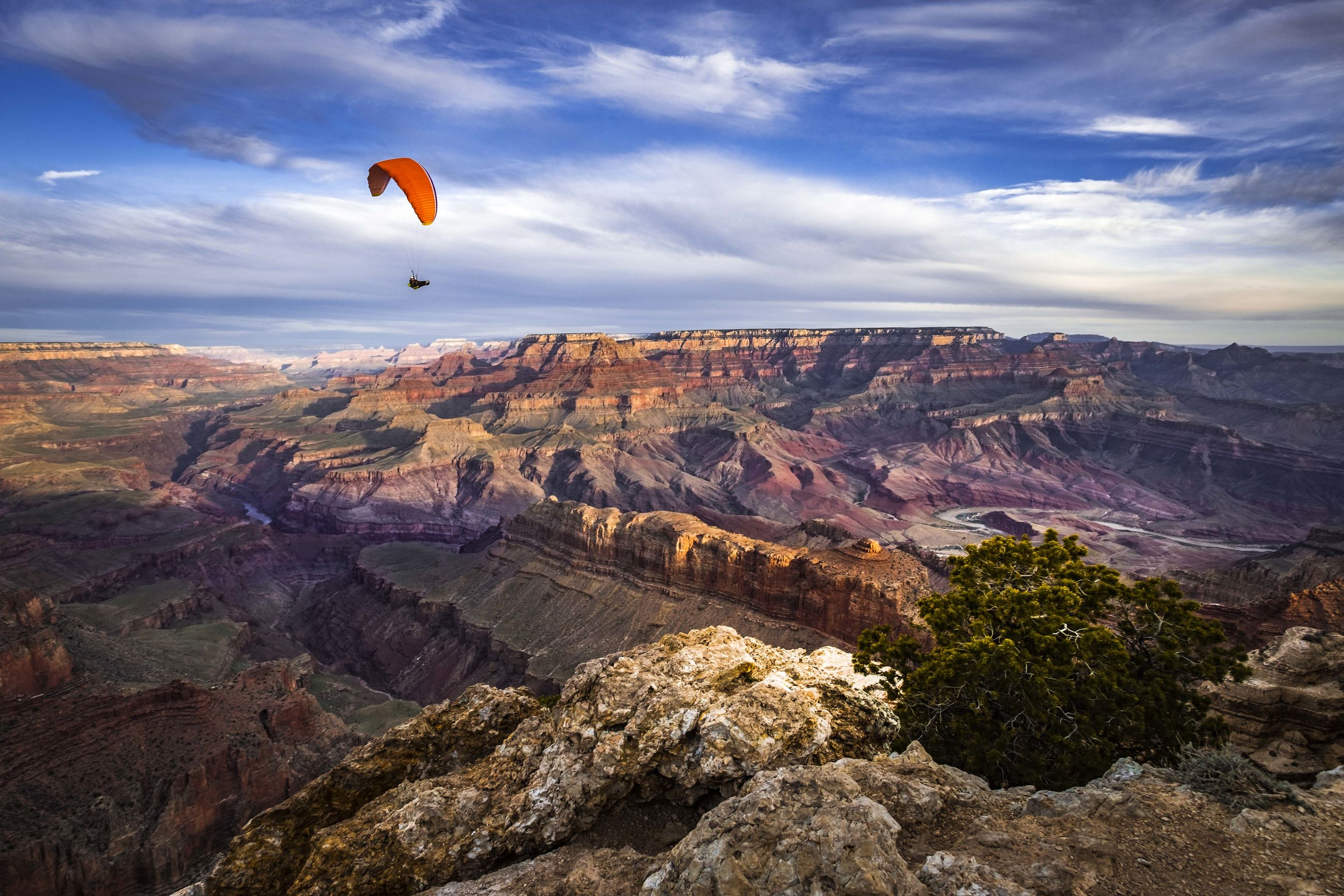adventure, beauty in nature, scenics - nature, cloud - sky, extreme sports, mountain, sky, parachute, non-urban scene, mid-air, sport, environment, flying, paragliding, landscape, tranquil scene, leisure activity, nature, tranquility, rock, mountain range, freedom, outdoors