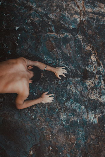 High angle view of shirtless man on rock