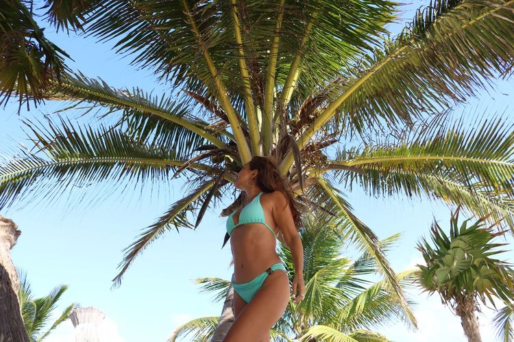 Low Angle View Of Mature Woman Standing Against Palm Trees