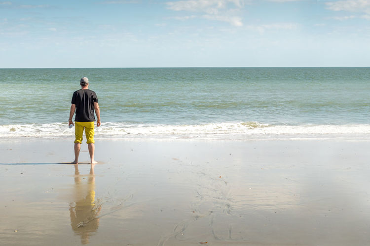 Enjoying the beach Man Tourist Vacations South Carolina Springtime Ocean USA Adult Sea Water Beach Land Horizon Over Water Horizon Rear View Real People Full Length One Person Sky Beauty In Nature Scenics - Nature Leisure Activity Standing Lifestyles Day Tranquil Scene Nature Outdoors Shorts