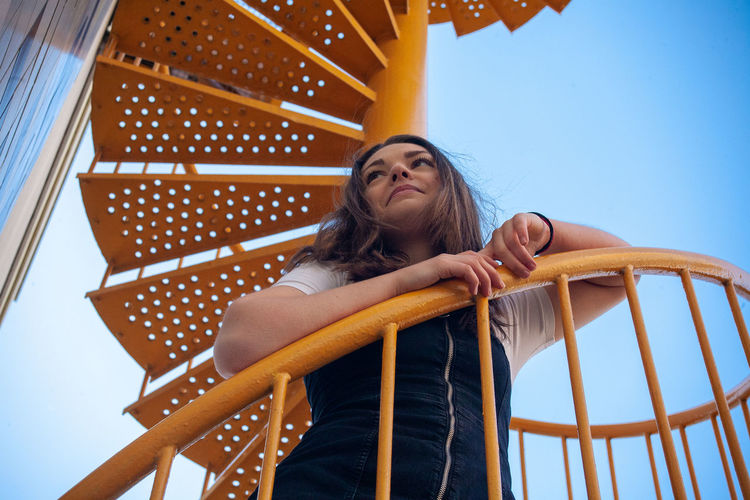 Low angle view of woman looking away while sitting on chair