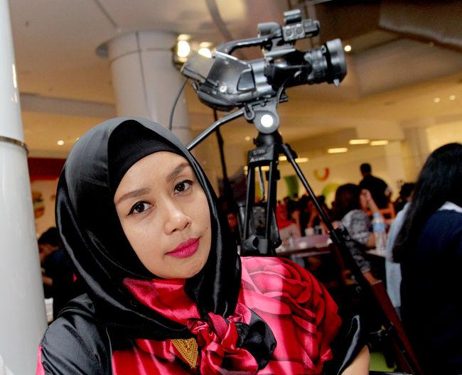 Portrait of woman sitting by camera on tripod