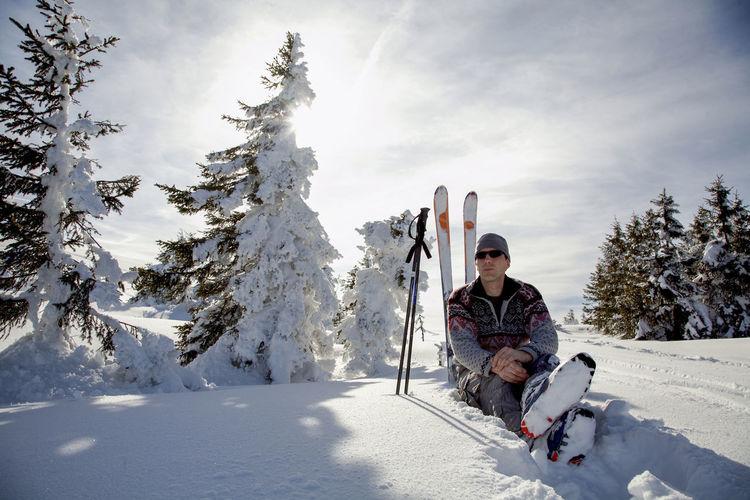 Full length of man sitting in snow against sky
