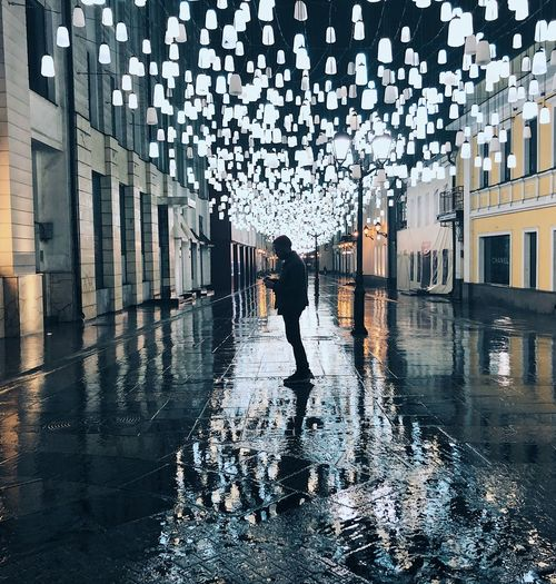 Full length of man walking on wet city street during rainy season