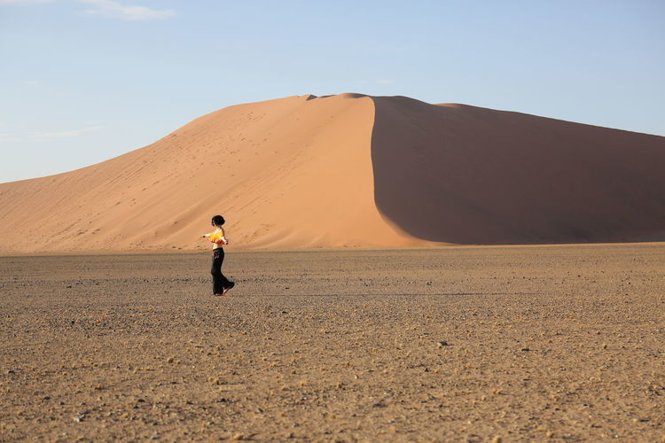 Woman walking on desert against sand dune