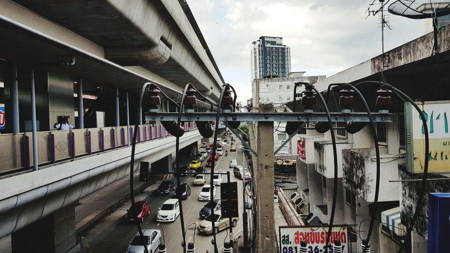 Road signal by bridge in city