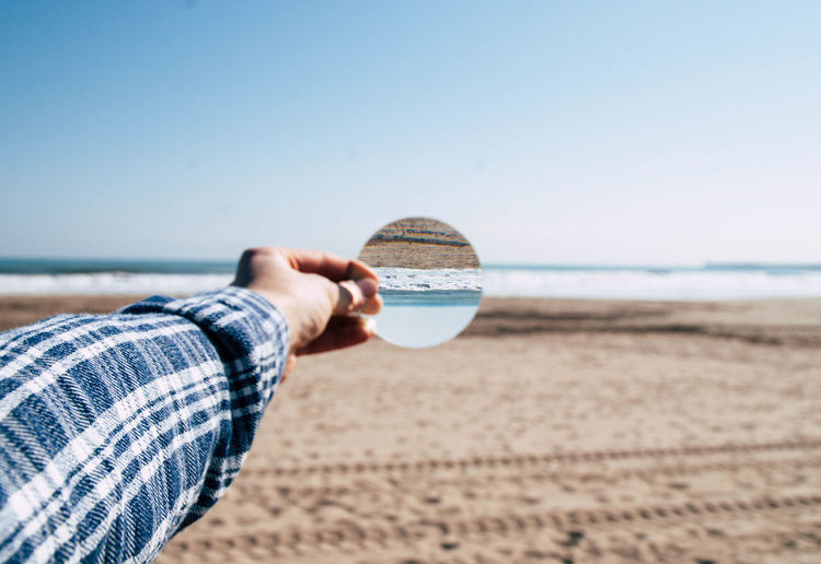 Cropped Hand Holding Mirror With Reflection Against Sea