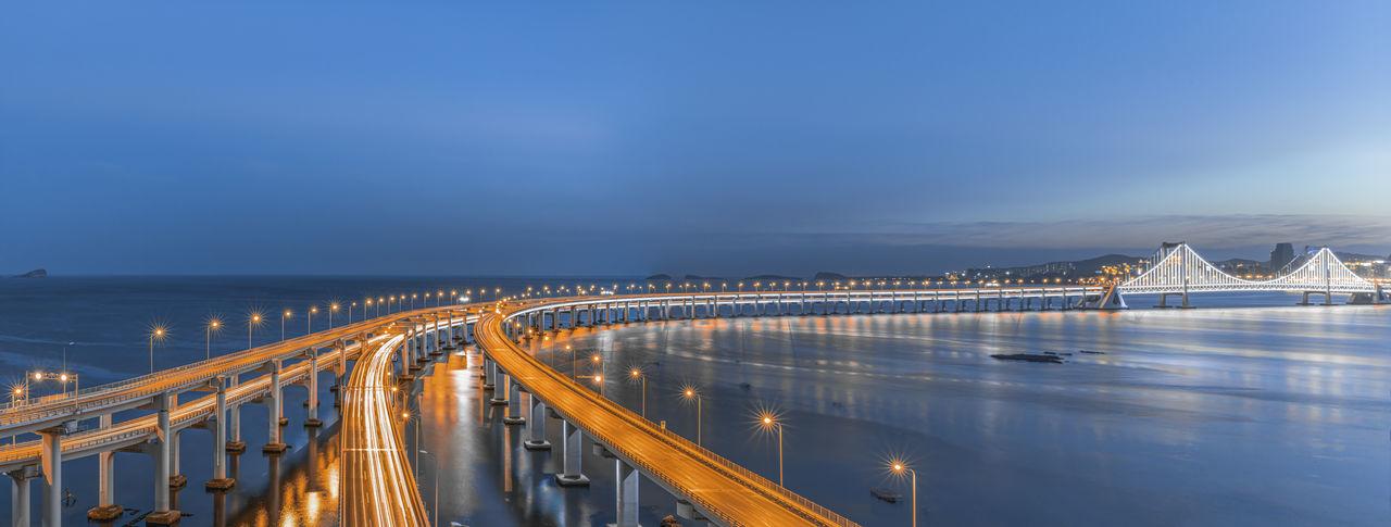 Illuminated bridge over sea against sky at night