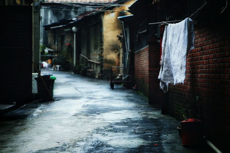 Alley amidst old houses during rainy season