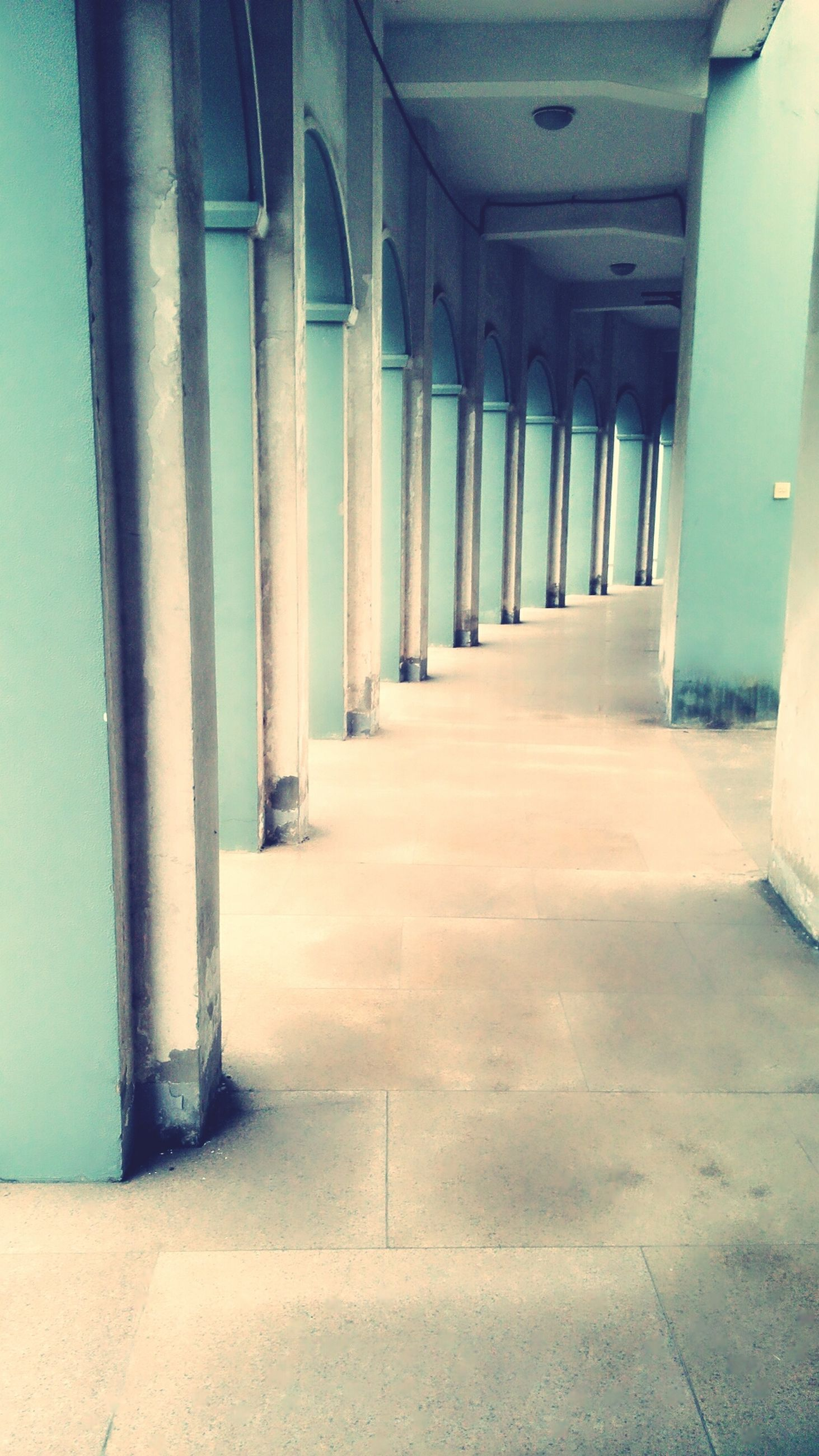 architecture, indoors, built structure, the way forward, corridor, in a row, empty, diminishing perspective, architectural column, flooring, column, absence, sunlight, narrow, building, vanishing point, day, no people, colonnade, tiled floor