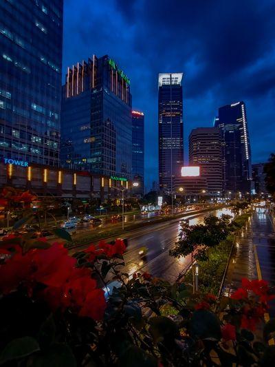 Illuminated modern buildings against sky at night