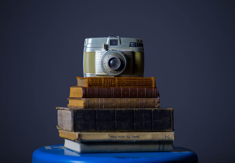 Close-up of old-fashioned camera on old books against black background