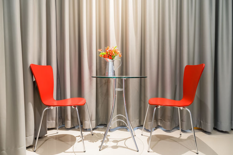 Empty chairs and table against curtain in room