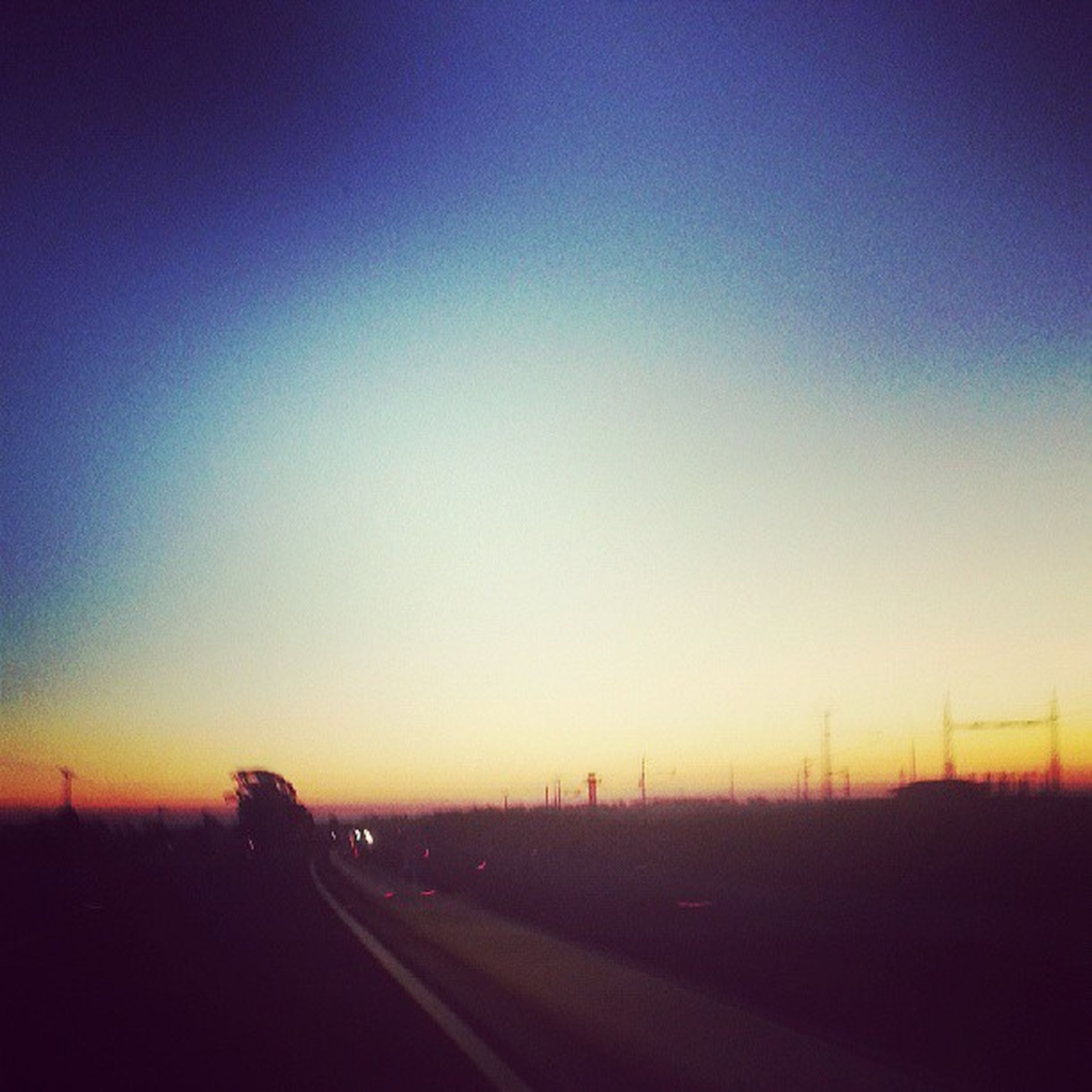 copy space, clear sky, sunset, landscape, tranquil scene, tranquility, road, silhouette, scenics, transportation, field, beauty in nature, nature, dusk, horizon over land, the way forward, blue, outdoors, no people, sky