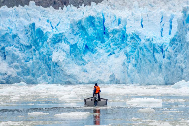 Rear View Of Man In Boat On Frozen Sea