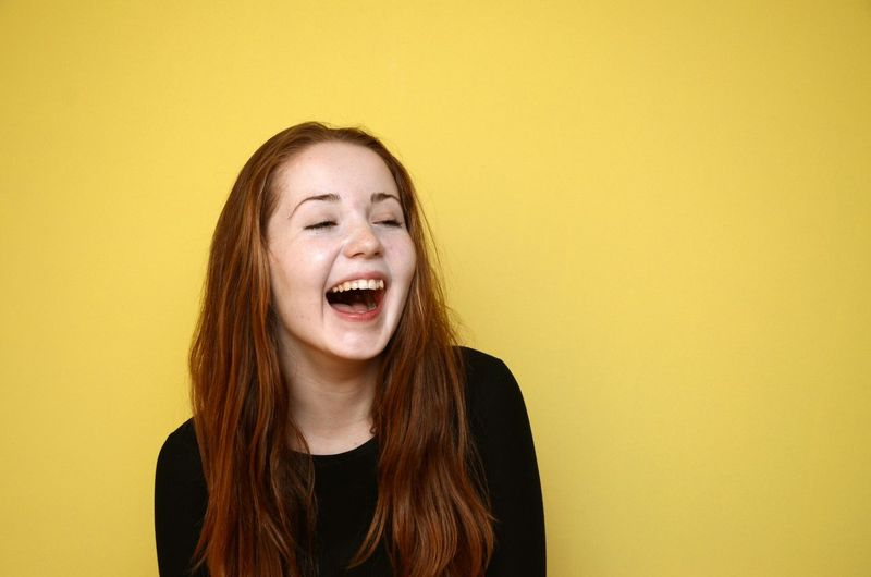 Cheerful Young Woman Against Yellow Background