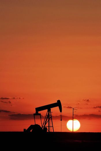 Orange setting sun behind a pump jack in the Permian Basin Texas Energy Texas Skies Desert Heat Oil And Gas Industry Midland, TX Oil Industry Permian Basin Sunset Solar Pump Jack Silhouette Sunset Oil Pump Industry Fuel And Power Generation Sky Orange Color Oil Well Copy Space Nature Environment No People Environmental Issues Sun Scenics - Nature Industrial Equipment