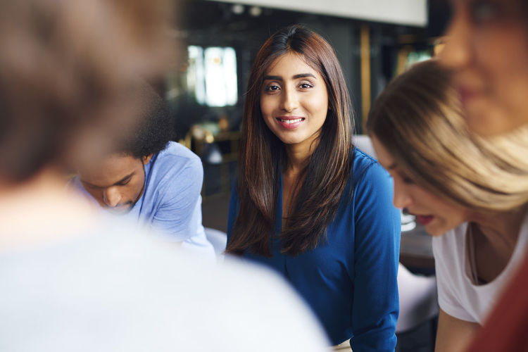 Portrait of smiling businesswoman in meeting with colleagues