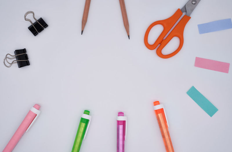 Directly above shot of multi colored pens with adhesive notes and scissors on gray background