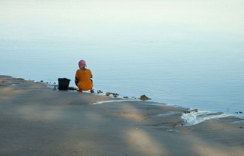 Rear view of woman crouching on sea shore