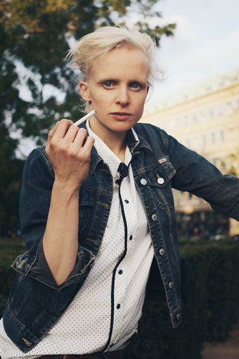 Mid adult woman holding cigarette in park