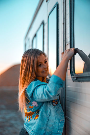 Side view of young woman standing by camper trailer