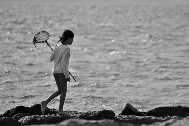 Side View Of Girl Carrying Butterfly Net On Shore