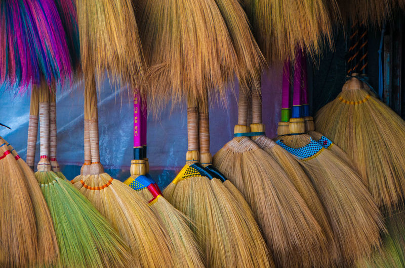 Close-up of brooms for sale at market stall