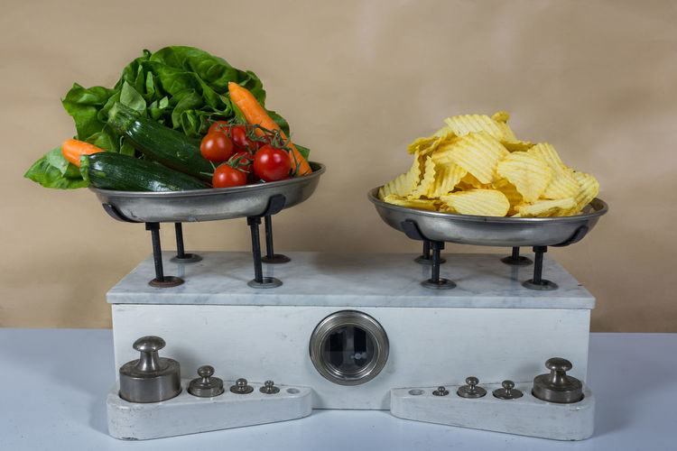 Close-up of potato chips and various vegetables on weight scale