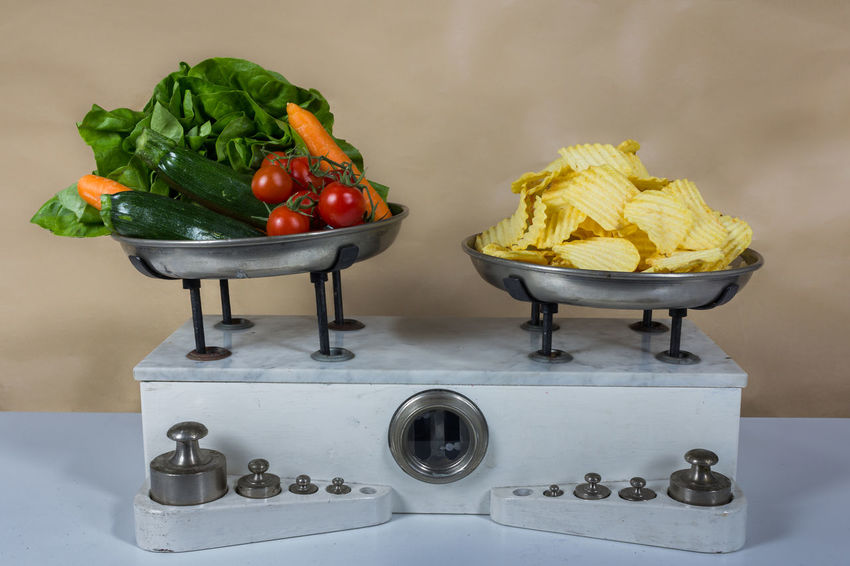 Balance with two metal plates with vegetable and chips Antique Balance Chips Diet Gram Imbalance Kilogram Measure, Measurement Metal Old Retro Vegetable Vintage, Toy, Old Photo Weight