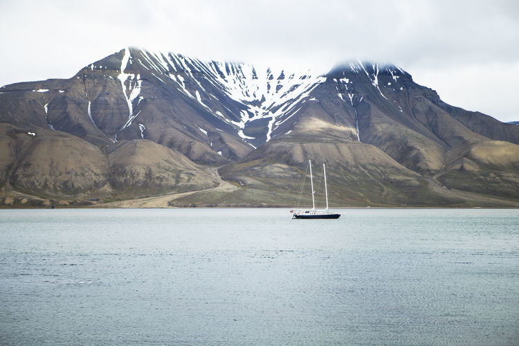 Sailboat on sea by snowcapped mountain against sky