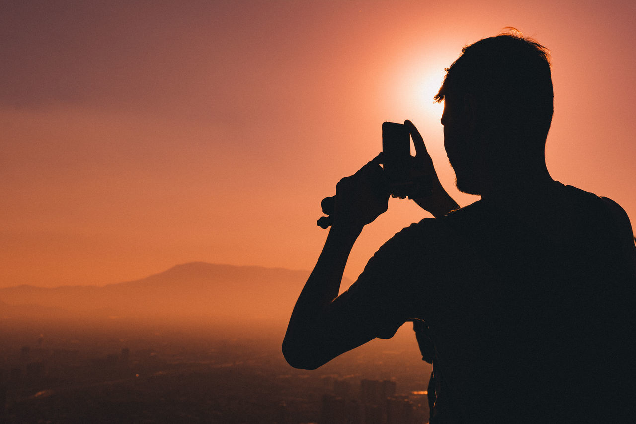 Rear view of silhouette man photographing against sky during sunset