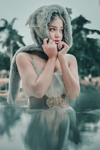 Digital composite image of young woman wearing fur hat in lake