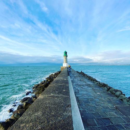 Full length of woman standing on pier against lighthouse