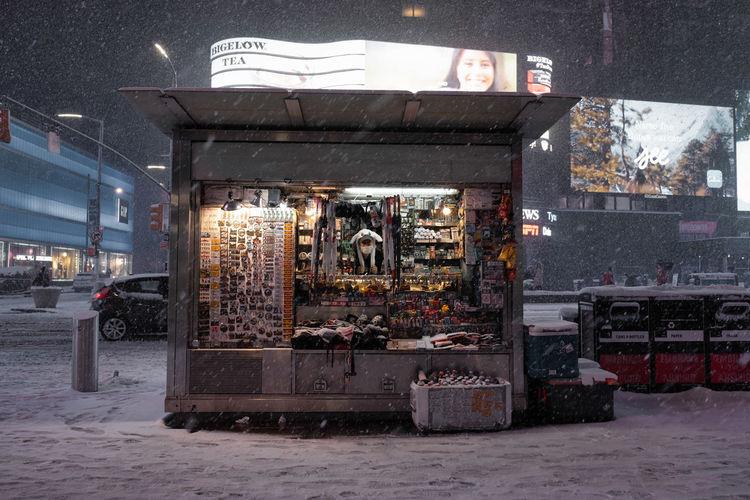 Illuminated street in city during winter