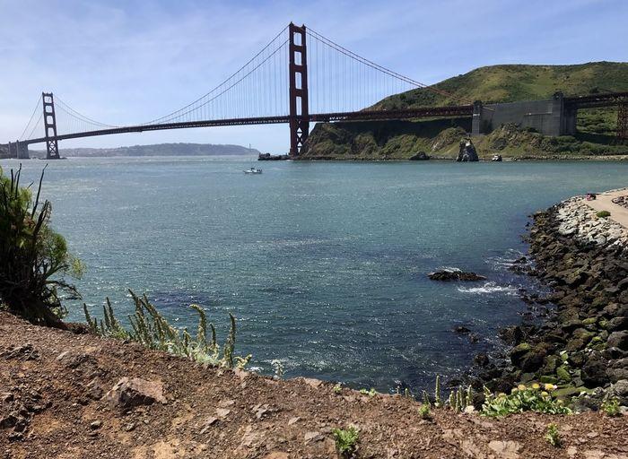 Suspension bridge over water against sky