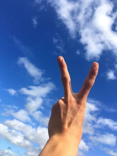 Close up of human hand against blue sky