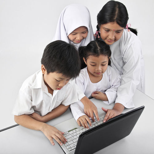 Friends Using Laptop Against White Background