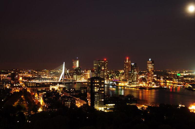 Erasmus Bridge Over Nieuwe Maas River In Illuminated City Against Sky