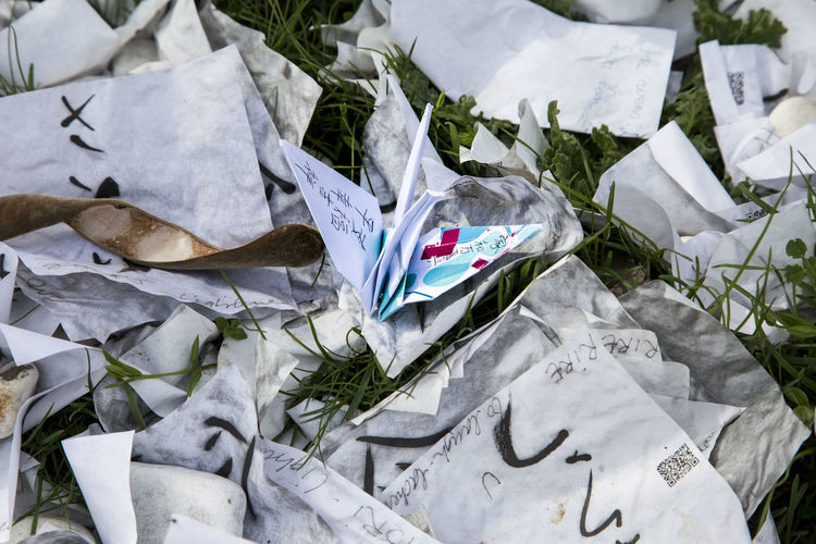 High angle view of paper crane amidst documents on field