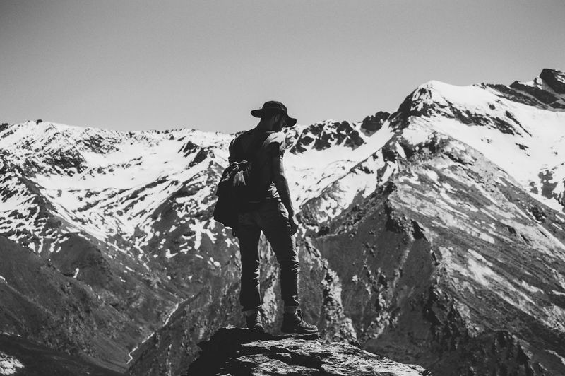 Man standing on snowcapped mountain against clear sky