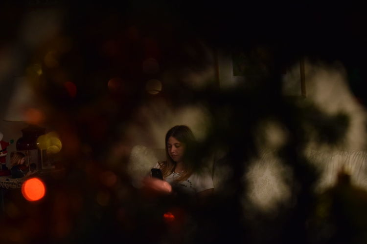Woman using mobile phone seen through christmas tree
