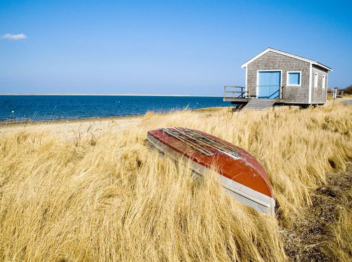 Upside down boat amidst grass by sea against sky