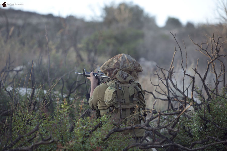 Rear View Of Soldier Aiming With Sniper On Field