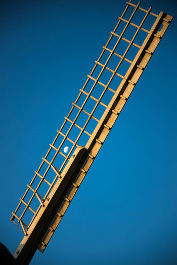 Low angle view of moon through a sail of a windmill against clear blue sky