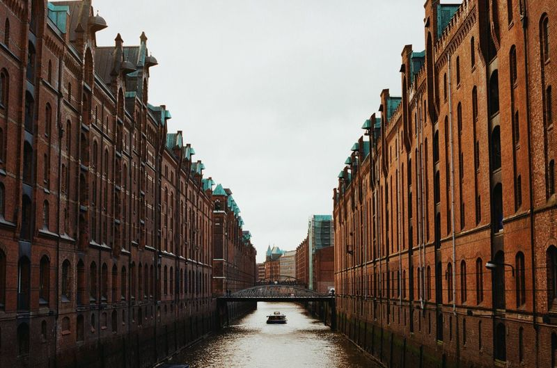 Canal amidst buildings against sky in city